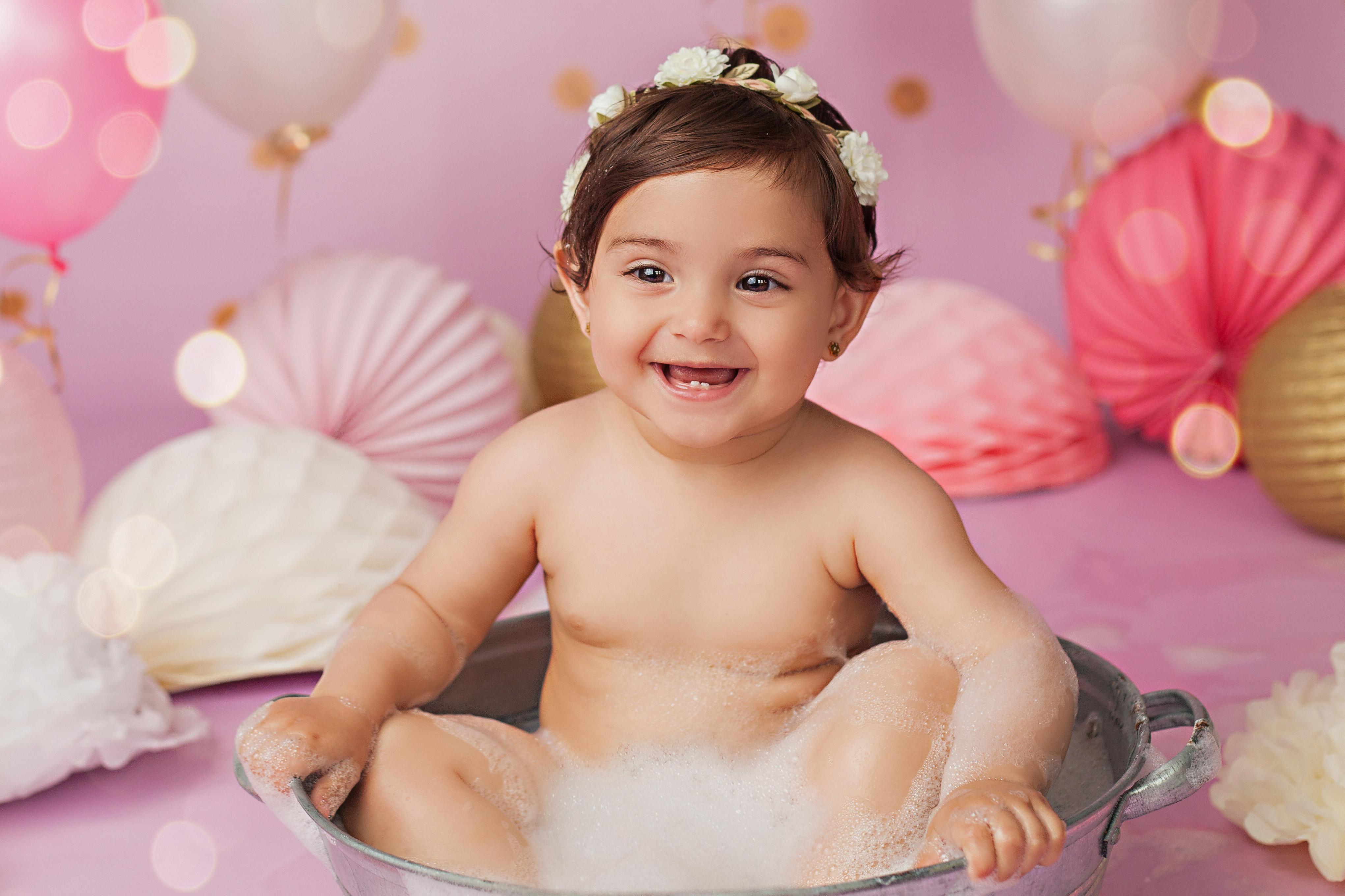 glückliches Baby Mädchen im Schaumbad Cake Smash